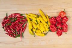 辣椒三品种在一张木桌上的 库存图片