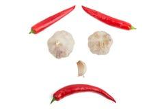 从辣椒和大蒜的面孔在白色背景 图库摄影