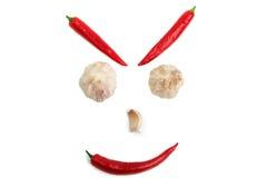 从辣椒和大蒜的面孔在白色背景 库存图片
