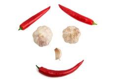辣椒和大蒜的面孔在白色背景 免版税图库摄影