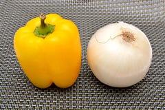 辣椒的果实黄色和葱在背景 免版税库存图片