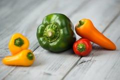 辣椒粉混合、甜微型红色,黄色和橙色胡椒和青椒在木背景 免版税库存照片