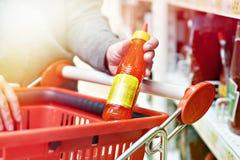 辣椒调味汁在手中在杂货店 免版税库存图片