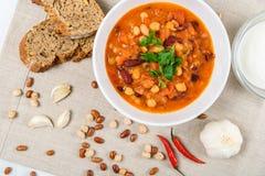 辣椒豆炖煮的食物、面包、红辣椒和大蒜 库存照片