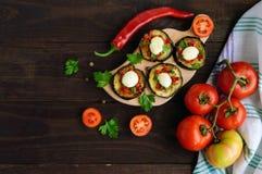 辣油煎的茄子切片用红辣椒、大蒜、草本和无盐干酪 库存照片