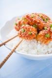 辣糖醋鸡用芝麻和米接近在蓝色背景 免版税图库摄影