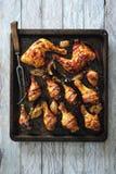 辣给上釉的和烟肉被包裹的鸡腿烘烤了用葱和辣椒 免版税库存照片