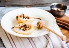 辣被烘烤的梨用核桃,蜂蜜,肉桂条,健康d 图库摄影