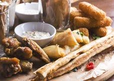 辣被烘烤的鸡翼、面包条用开胃菜和调味汁 库存照片