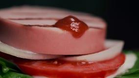 辣辣味番茄酱加到在汉堡的香肠,做汉堡,肉汉堡,不健康的食物,快餐 股票视频