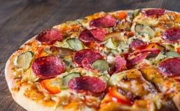 辣香肠烘饼用无盐干酪乳酪、蒜味咸腊肠、烟肉、西红柿酱、胡椒、香料和酱瓜 在木的意大利比萨 库存照片