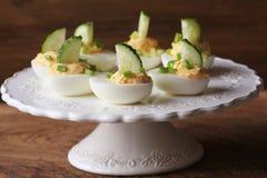 辣deviled鸡蛋装饰用黄瓜和韭葱在白色板材 免版税库存照片
