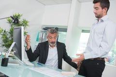辩论的商人,当看在办公室里时的膝上型计算机 免版税图库摄影