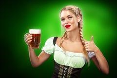 边界日pattys st 年轻性感的慕尼黑啤酒节女服务员,穿一件传统巴法力亚礼服,在蓝色的服务的大啤酒杯 库存照片