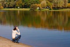 边界河坐的妇女 免版税库存图片