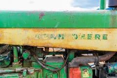 边的老,被佩带在经典拖拉机下,显示约翰Deere商标字标的残余在绿色和黄色和拖拉机 免版税图库摄影