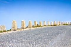 边石被安置在一条弯曲的路的边缘由海洋 免版税图库摄影