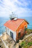 边缘和蓝色海洋的老房子 库存照片