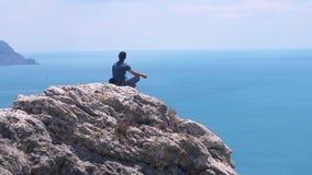 边缘的思考的人,坐在岩石顶部反对蓝色海背景,并且天空和鸟在慢飞行 股票视频