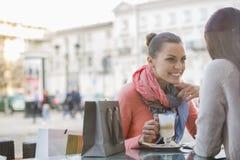 边路咖啡馆的女性朋友 免版税库存图片