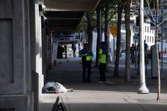 边路的西雅图街市大使在无家可归的人旁边 库存图片