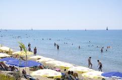 边,土耳其, 2013年7月29日:晒日光浴和游泳在地中海的游人在边东部海滩在安塔利亚省的 库存照片