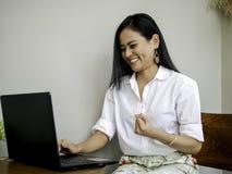 达到目标的成功的美丽的亚裔企业家,举在拳头的手有令人激动的和微笑的面孔的 免版税库存照片