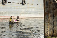 达卡,孟加拉国, 2017年2月24日:两个人在河乘坐他们的木小船 免版税库存照片