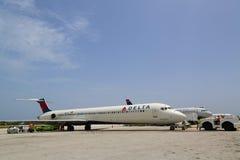 达美航空麦克当诺道格拉斯公司MD-80和全美航空公司在欧文・罗伯茨国际机场喷射在大开曼 免版税库存照片