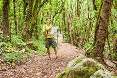 迁徙与地图的远足者在森林里 免版税库存图片