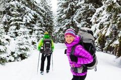 迁徙在冬天森林的夫妇愉快的远足者 免版税库存图片