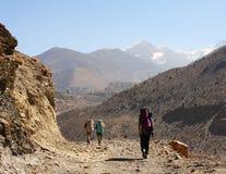 迁徙在喜马拉雅山的小组背包徒步旅行者 免版税库存图片