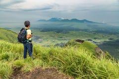迁徙在小山上面和观看的阿苏山火山的远足者  库存图片