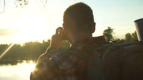 迁徙在森林里的男性背包徒步旅行者,拍摄美好的日落在湖附近 影视素材