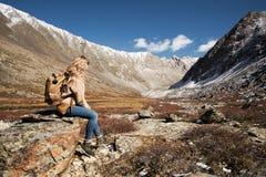 迁徙在狂放的山的妇女背包徒步旅行者 免版税库存图片