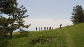 迁徙在绿色高地的旅游小组,当夏天旅行时 走在青山的旅行的人民 上升  股票视频