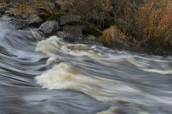 迅速河流程和冰砾与下落的叶子 库存照片