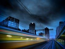 迅速火车和现代城市在晚上 免版税库存图片