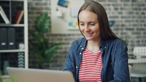 迅速移动在使用膝上型计算机的美丽的少女画象在然后微笑的工作 股票视频