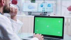 迅速移动在膝上型计算机的射击有绿色屏幕大模型的 股票视频