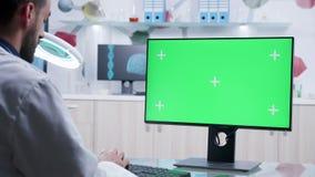 迅速移动研究有绿色屏幕大模型的计算机的医生射击 股票视频