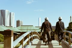 过一座桥梁在Hamarikyu庭院里,东京,日本的两名日本建筑工人 图库摄影