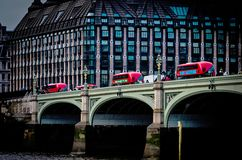 过威斯敏斯特桥梁的三辆红色公共汽车 库存图片