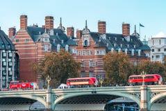 过威斯敏斯特桥梁,伦敦-英国的三辆红色公共汽车 库存图片
