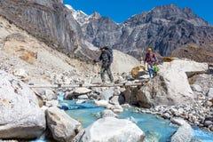 过山河投掷木桥的小组远足者 免版税库存照片