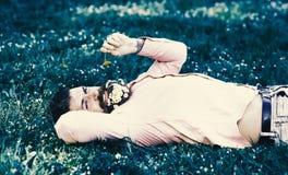 过敏和抗组胺概念 有雏菊花的有胡子的人在胡子在grassplot,草背景放置 308个黄铜弹药筒报道了遥远的空的地面下跪人步枪射击吊索雪目标冬天 图库摄影