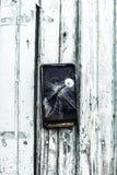 过时技术的概念:手机钉牢了到篱芭一个大钉子 免版税库存照片