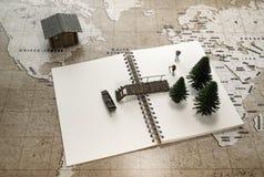 过有一条小船的两缩样老木桥在有一个房子的笔记本世界地图的 库存图片