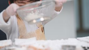 过滤与过滤器筛子滤锅的逗人喜爱的矮小的亚裔男孩特写镜头面团面粉在家庭厨房为准备对烘烤的面包店和c 股票录像
