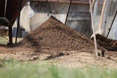 过滤地球通过筛子 电烙铁锹,铁桶,小铁圈子 通过在堆的草黏土 库存照片